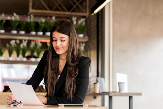 Mujer de negocios morena leyendo documento