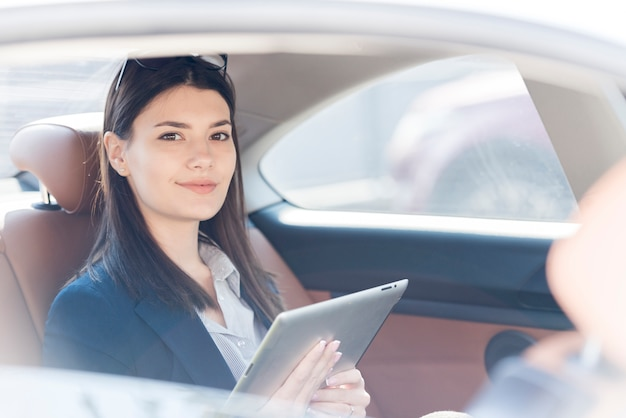 Mujer de negocios morena posando dentro de un coche