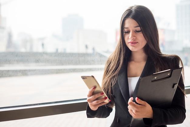 Mujer de negocios morena usando su móvil