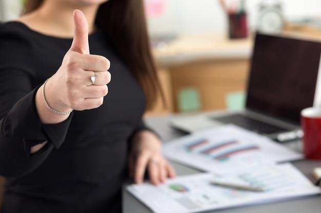 Mujer de negocios muestra el pulgar hacia arriba sentado en su oficina de cerca. concepto perfecto de calidad de bienes o servicios. cliente satisfecho. bien símbolo