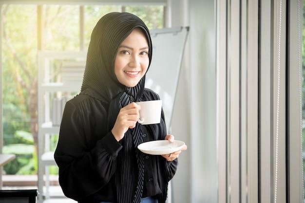 Mujer de negocios musulmán hermosa en vestido negro que bebe una taza de café en el cierre de la oficina para arriba.