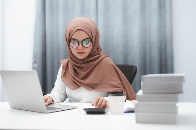 Mujer de negocios musulmana asiática con hijab marrón trabajando con ordenador portátil en la oficina en casa.