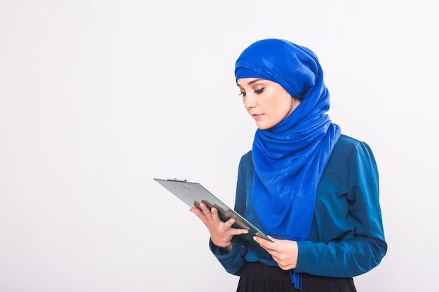 Mujer de negocios musulmana asiática joven que sonríe y que sostiene el documento de archivo