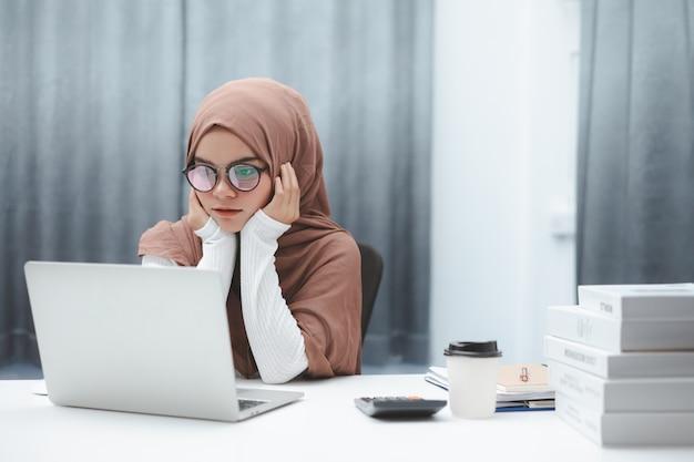 Mujer de negocios musulmana atractiva que trabaja en la oficina en casa.