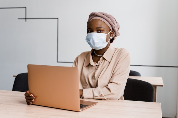 Mujer de negocios musulmana negra en máscara médica con ordenador portátil.
