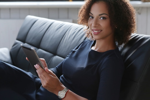 Mujer de negocios negra en estricto vestido negro revisando sus correos electrónicos en la tableta