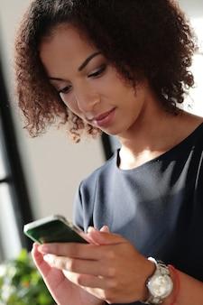 Mujer de negocios negra en estricto vestido negro revisando sus correos electrónicos en el teléfono