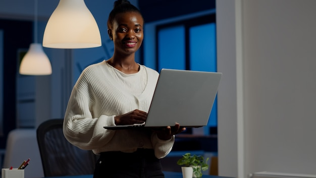 Mujer de negocios negra mirando al frente sonriendo sosteniendo portátil de pie cerca del escritorio en la empresa de nueva creación a altas horas de la noche