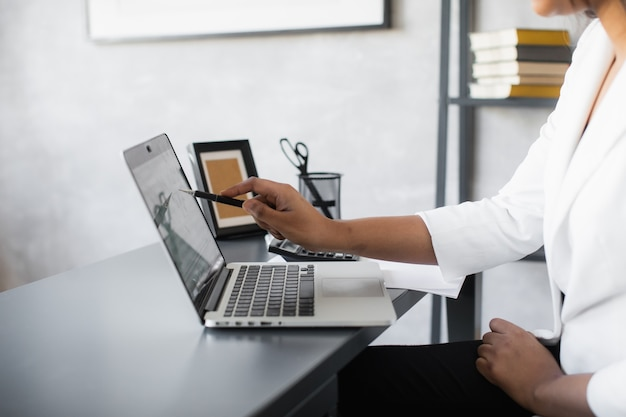 Mujer de negocios negra usando la computadora portátil para analizar los datos del mercado de valores gráfico de comercio de divisas bolsa de valores comercio concepto de inversión financiera en línea de cerca