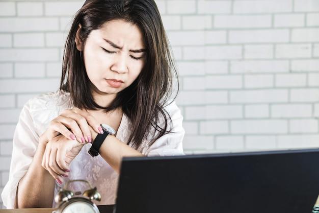 Mujer de negocios ocupada que controla el tiempo en su reloj