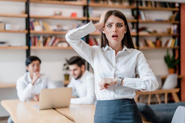 Mujer de negocios en la oficina preocupada por falta de tiempo