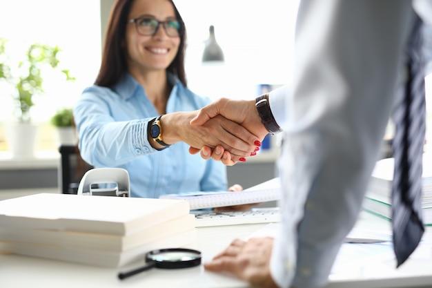 La mujer de negocios en oficina sacude las manos con el socio comercial.