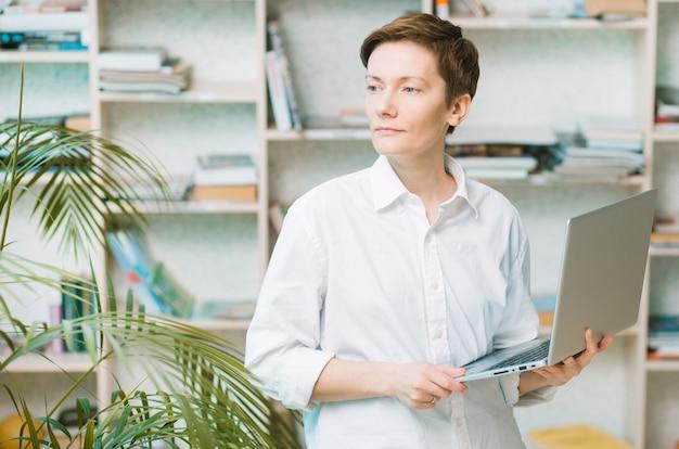 Mujer de negocios con ordenador portátil en un amplio estudio con una palmera y estantes mirando