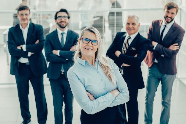 Mujer de negocios orgullosa de pie delante de un equipo empresarial.