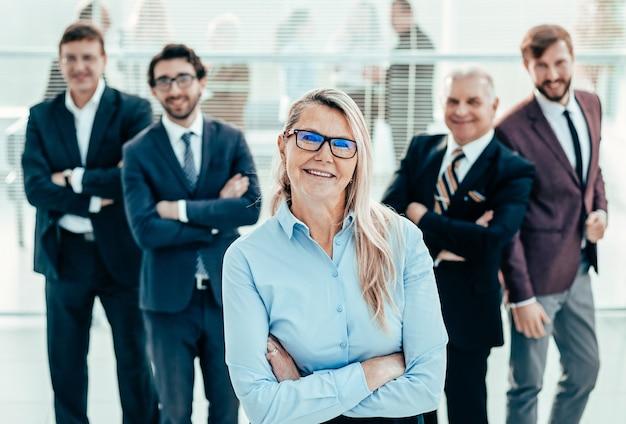 Mujer de negocios orgullosa de pie delante de un equipo empresarial