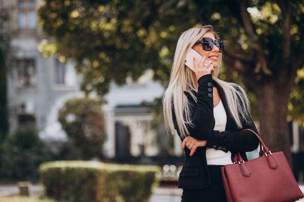 Mujer de negocios en el parque con bolsa roja