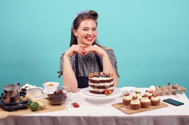 Mujer de negocios pastelero al horno bizcocho con relleno blanco, decorado con bayas