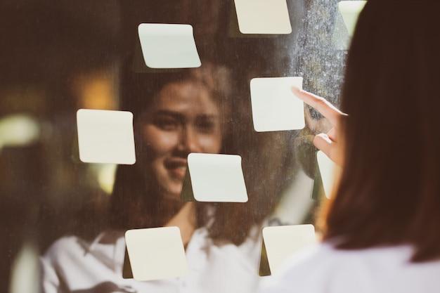 Mujer de negocios pegue papel en el espejo para recordar el trabajo esencial que debe hacer.