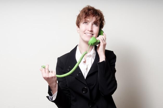 Mujer de negocios de pelo corto éxito usando teléfono verde