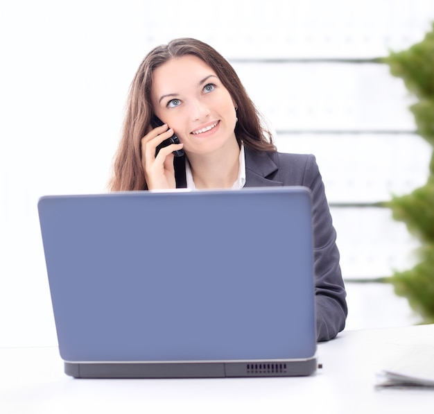 Mujer de negocios pensativa en la oficina, la conversación por teléfono, sonriendo.