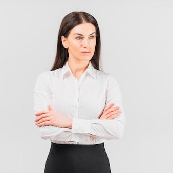 Mujer de negocios pensativa que se coloca con los brazos cruzados
