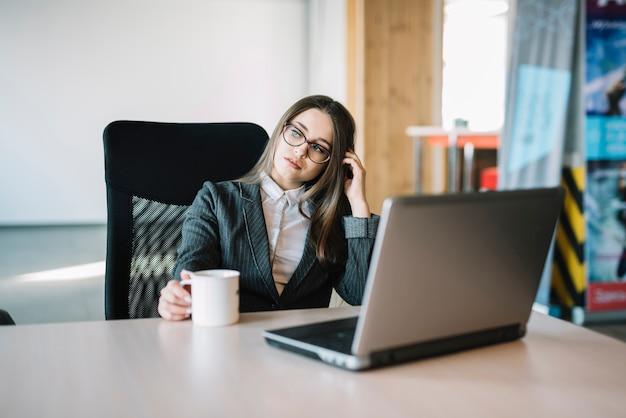 Mujer de negocios pensativa que se sienta en la tabla con el ordenador portátil
