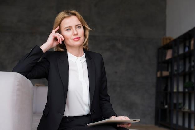 Mujer de negocios pensativa que se sienta con la tableta