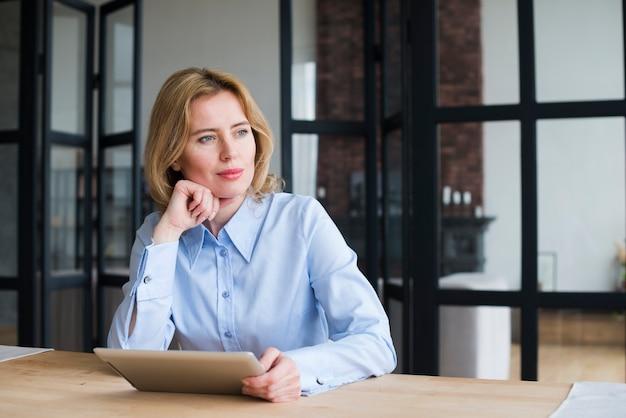 Mujer de negocios pensativa que usa la tableta en la tabla