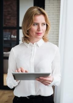 Mujer de negocios pensativa que usa la tableta