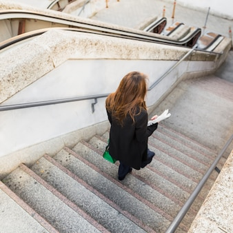 Mujer de negocios con periódico caminando por las escaleras
