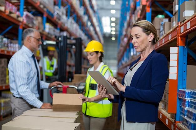 Mujer de negocios de pie en frente del trabajador del almacén en el almacén