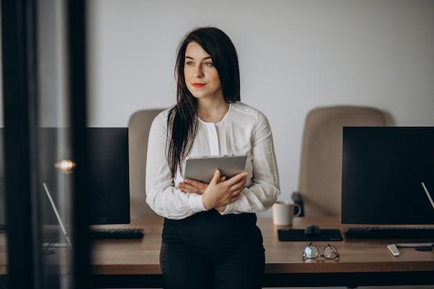 Mujer de negocios con pie de tableta en la oficina