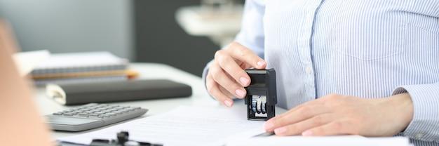 Mujer de negocios poniendo sello en el documento en la oficina de trabajo de primer plano con el concepto de documentos