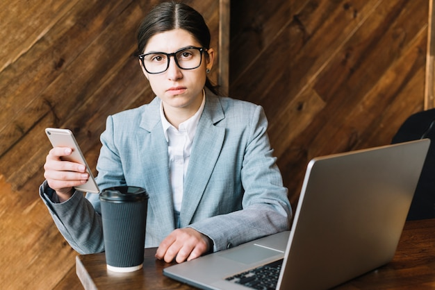 Mujer de negocios con portátil y smartphone en cafetería