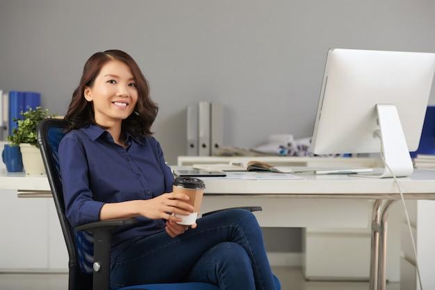 Mujer de negocios, posar, en, silla de la oficina