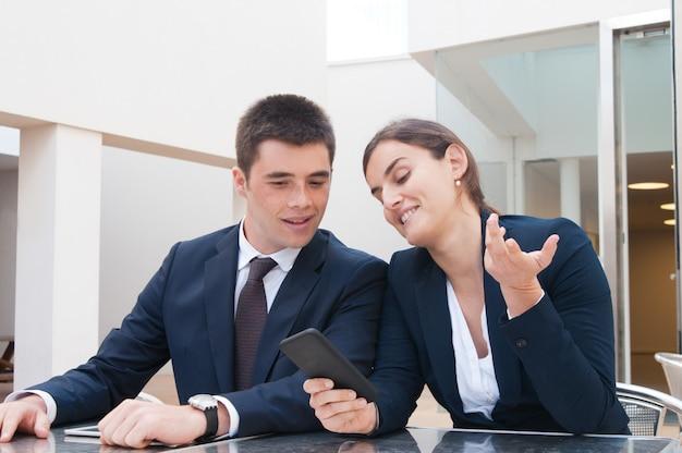 Mujer de negocios positiva que muestra la pantalla del teléfono inteligente al colega