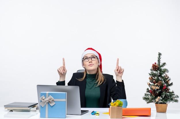 Mujer de negocios positiva con sombrero de santa claus sentado en una mesa con un árbol de navidad y un regalo apuntando arriba sobre fondo blanco.