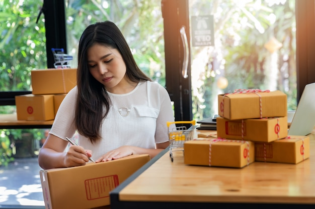 La mujer de negocios prepara la caja del paquete de producto para entrega al cliente.