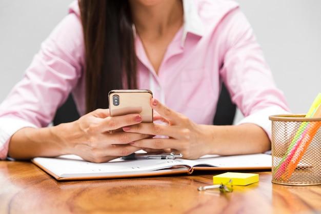 Mujer de negocios que controla su teléfono