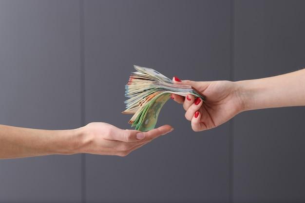 Mujer de negocios que entrega mucho dinero en efectivo al primer colega. concepto de ofertas rentables