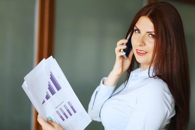 Mujer de negocios que habla en el teléfono móvil, sonriendo y mirando a la cámara. poca profundidad de campo.