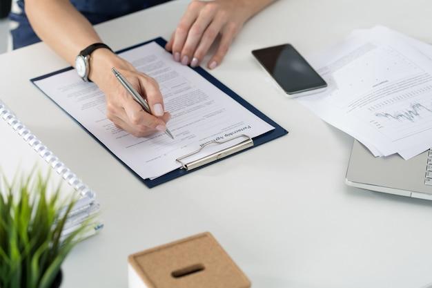 Mujer de negocios que llena el acuerdo de asociación en blanco. concepto de negocio y asociación