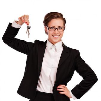 Mujer de negocios que lleva a cabo llaves sobre el fondo blanco