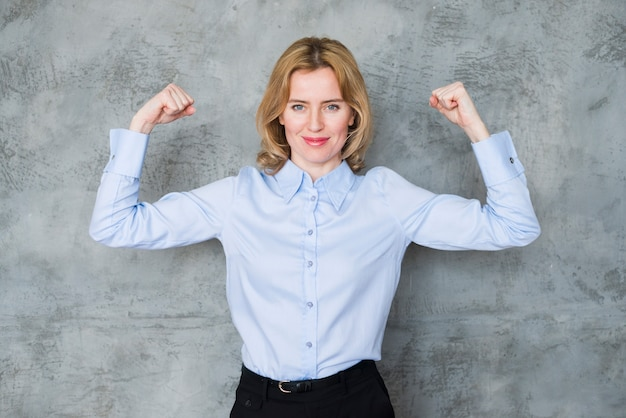 Mujer de negocios que muestra los músculos del brazo