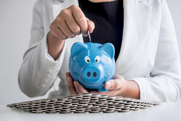 La mujer de negocios que pone la moneda en la hucha azul para planificar intensifica el negocio para obtener ganancias y ahorrar con el concepto de hucha