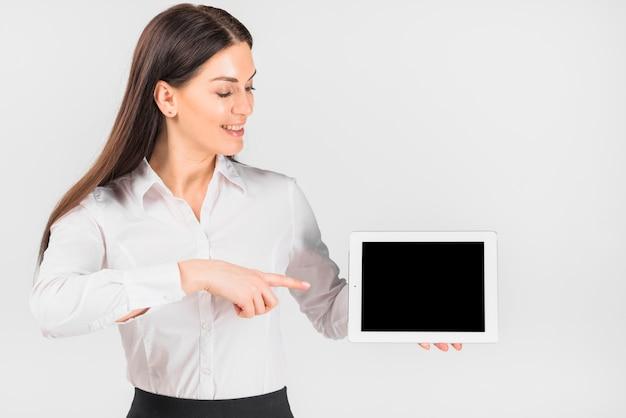 Mujer de negocios que señala el dedo en la tableta con pantalla en blanco