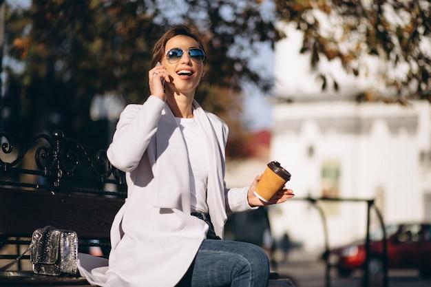 Mujer de negocios que se sienta en un banco con café de consumición del teléfono