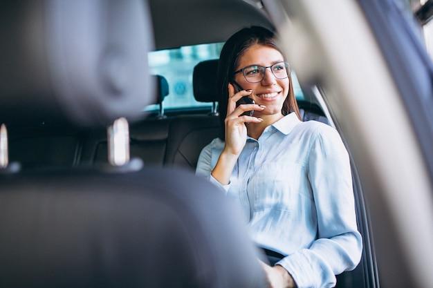 Mujer de negocios que se sienta en coche y que usa el teléfono