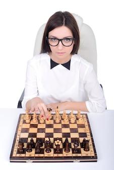 Mujer de negocios que se sienta delante de ajedrez y que planea.