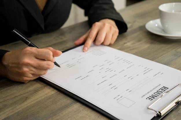 Mujer de negocios que solicita trabajo escribe en el currículum de la compañía